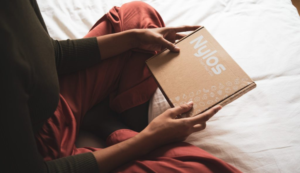 person in red long sleeve shirt holding brown book